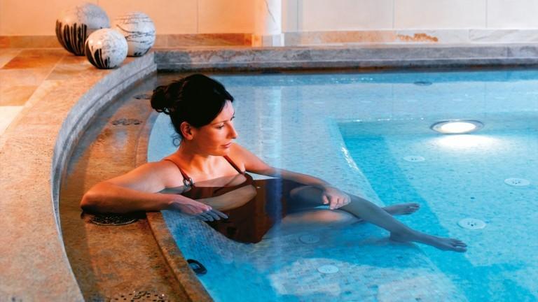 Eine Frau im Jacuzzi im hotel madlochblick beim Wellness.
