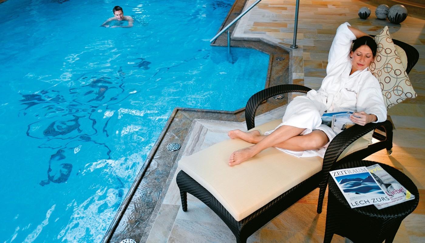 Eine schöne Frau im Liegestuhl am Pool des hotel & chalet madlochBlick.