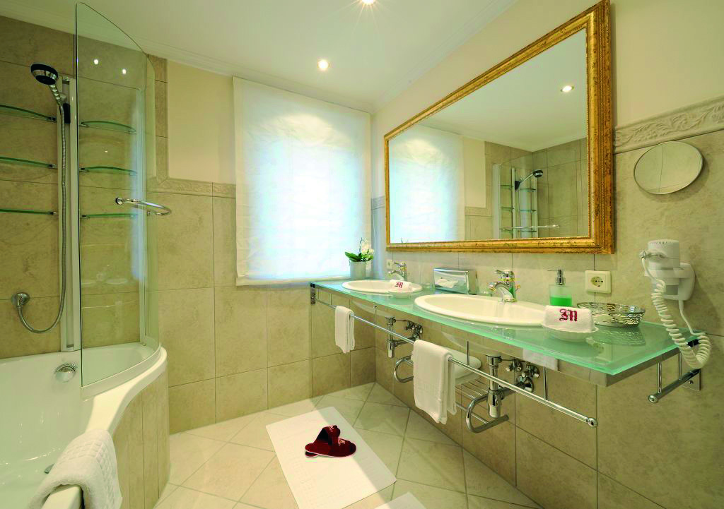 Badezimmer mit Doppelwaschbecken in der Junior Suite Kriegerhorn im hotel Madlochblick.