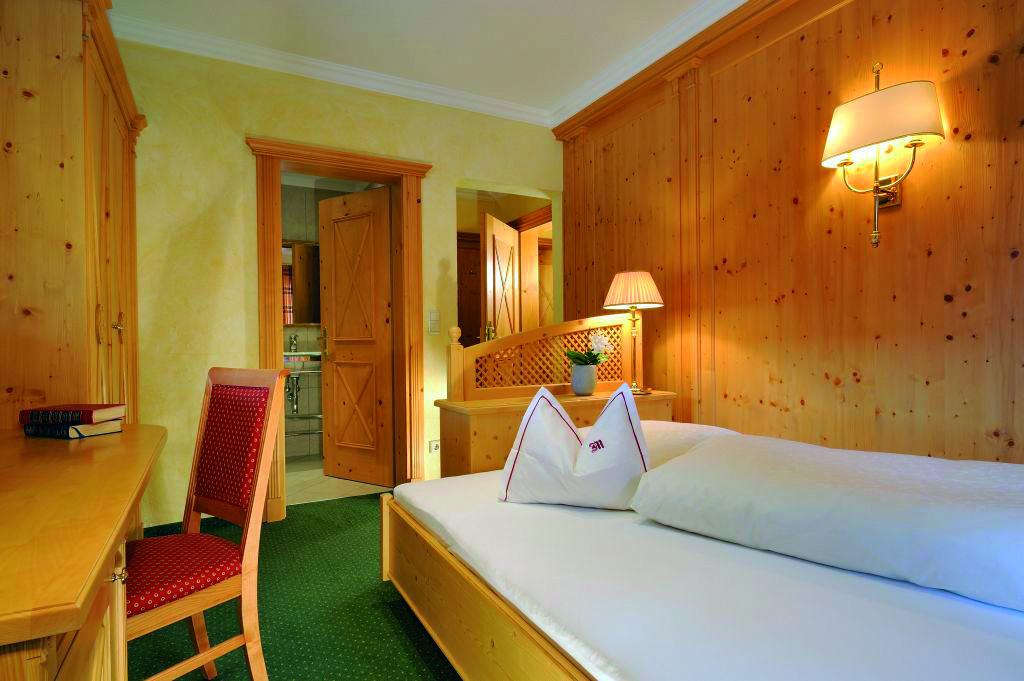 Das Einzelzimmer Wöster mit warmen Holz und gemütlichem Einzelbett im Hotel und Chalet madlochblick.