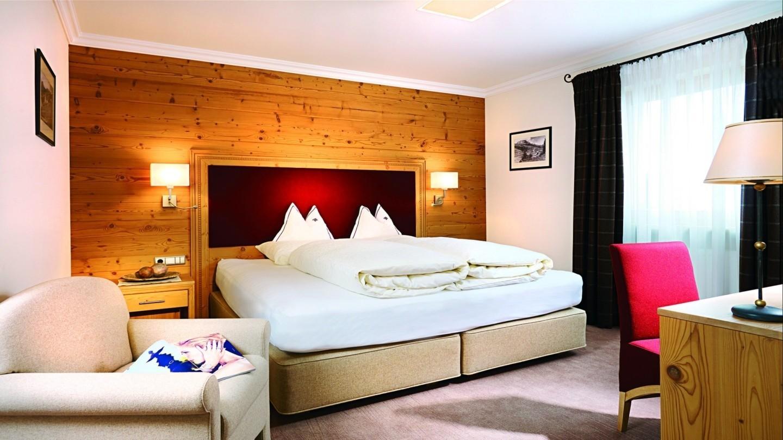 Suite Karhorn im Hotel MadlochBlick mit hellem Holz, warmen Farben und großem Fenster.