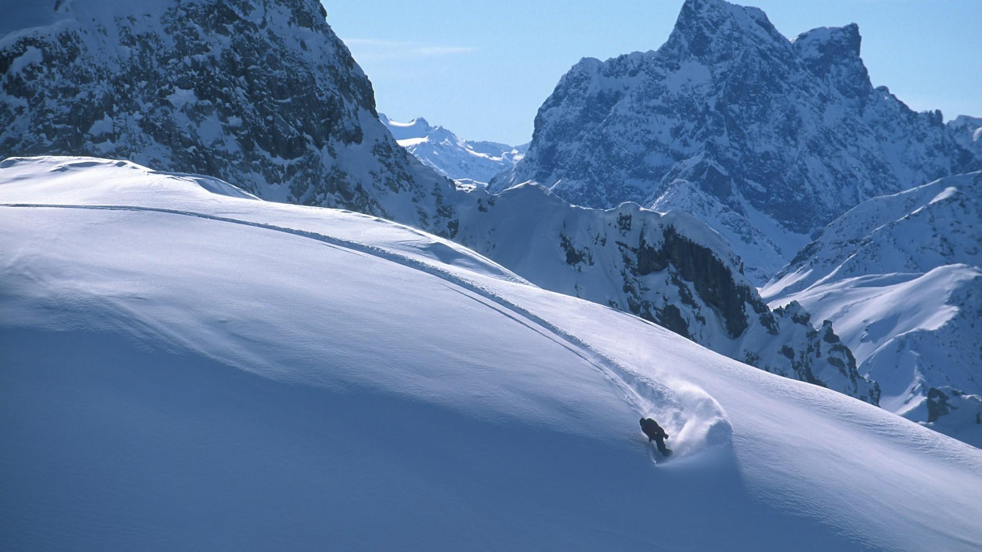 Snowboarder am Arlberg im frischen Powder beim Ziehen der ersten Tracks.