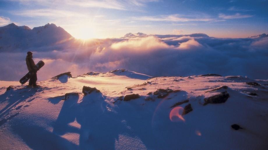 Snowboarder am Gipfel des Berges bei Sonnenuntergang.