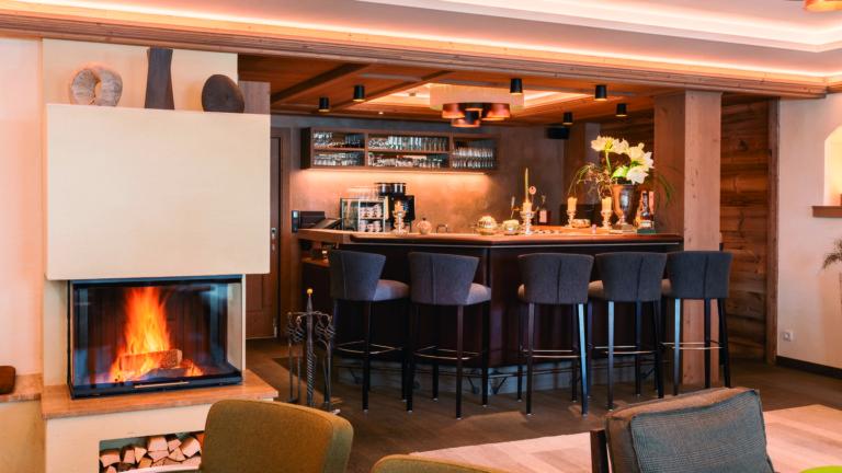 Die Bar im hotel madlochBlick mit Barbestuhlung, gedimmten Licht und einem offenem Feuer.