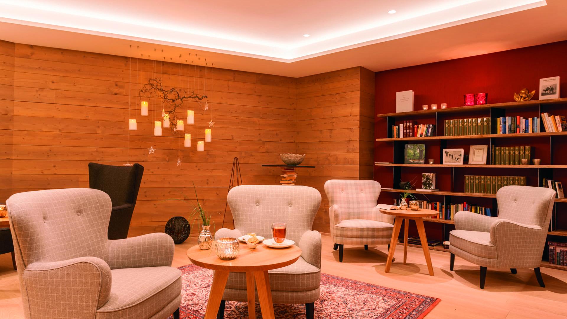 Bibliothek und Leselounge im hotel madlochBlick mit schönen Polstermöbeln und Holzvetäfelung.