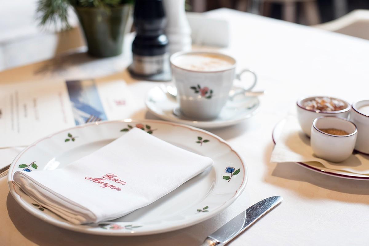 Ein Frühstücksgedeck mit Kaffee un einer Guten-Morgen-Serviette.