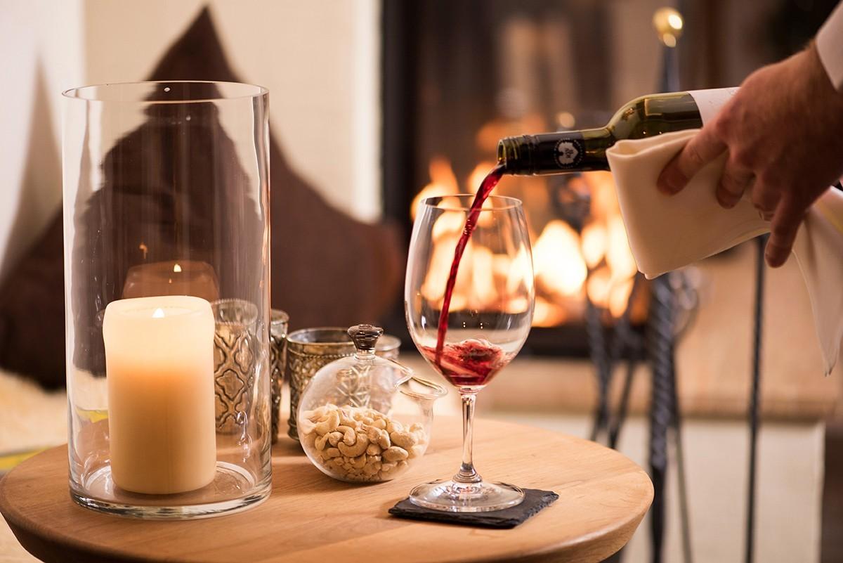 Ein Glas Rotwein vor dem knisternden Kaminfeuer serviert im Hotel MadlochBlick.