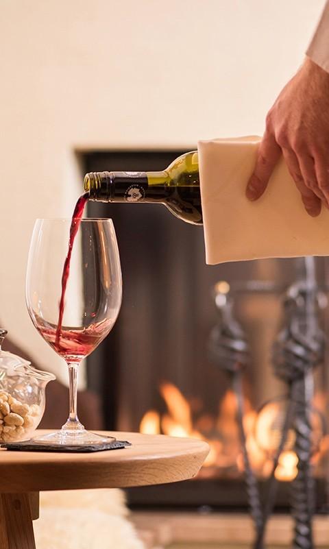 Ein Glas Rotwein vor dem knisternden Kamin nach einem delikaten Abendessen im hotel & chalet madlochBlick.