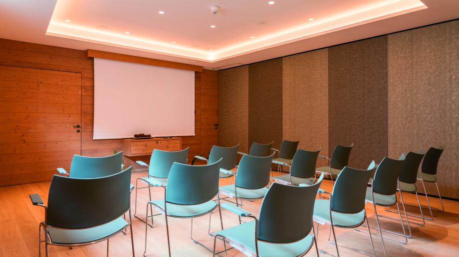 Seminarraum im hotel madlochBlick mit Kinobestuhlung und Leinwand.