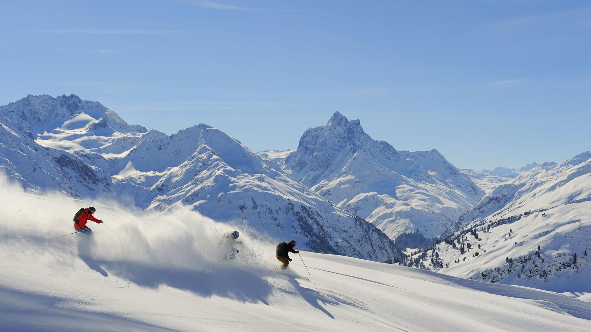 Drei Skifahrer am Arlberg beim Ziehen der ersten Tracks im Neuschnee.