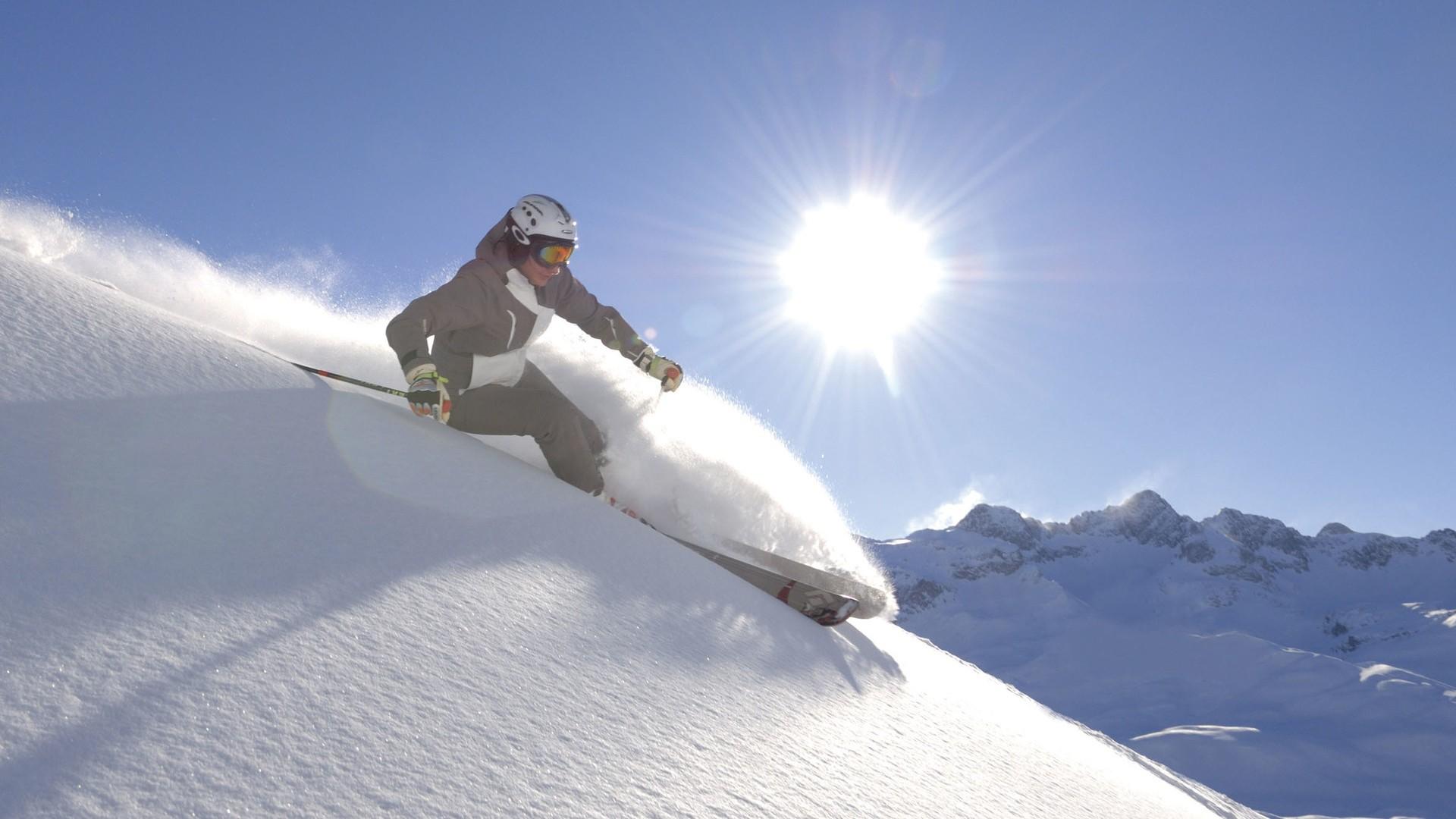 Skifahrerin auf unberührter Piste vor strahlendem Sonnenschein.