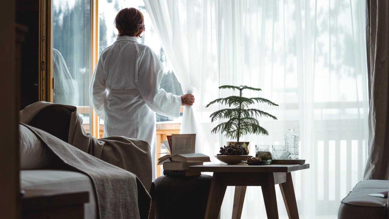 Eine Frau im Bademantel im Familienzimmer BergBlick, die aus dem Fenster schaut.