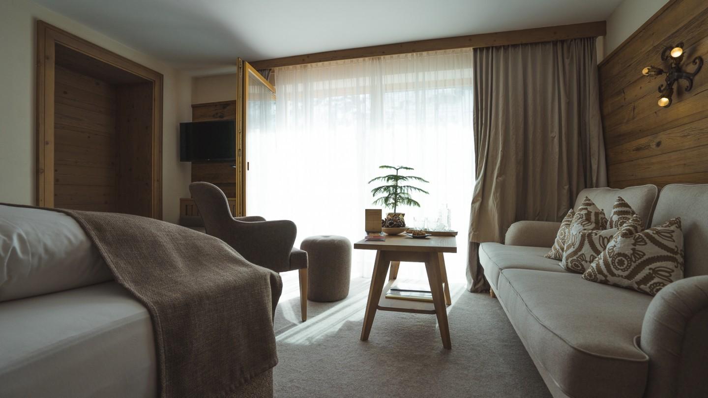 Familienzimmer Bergblick mit Bett, Sofa, Tisch und Blick zum Balkon.