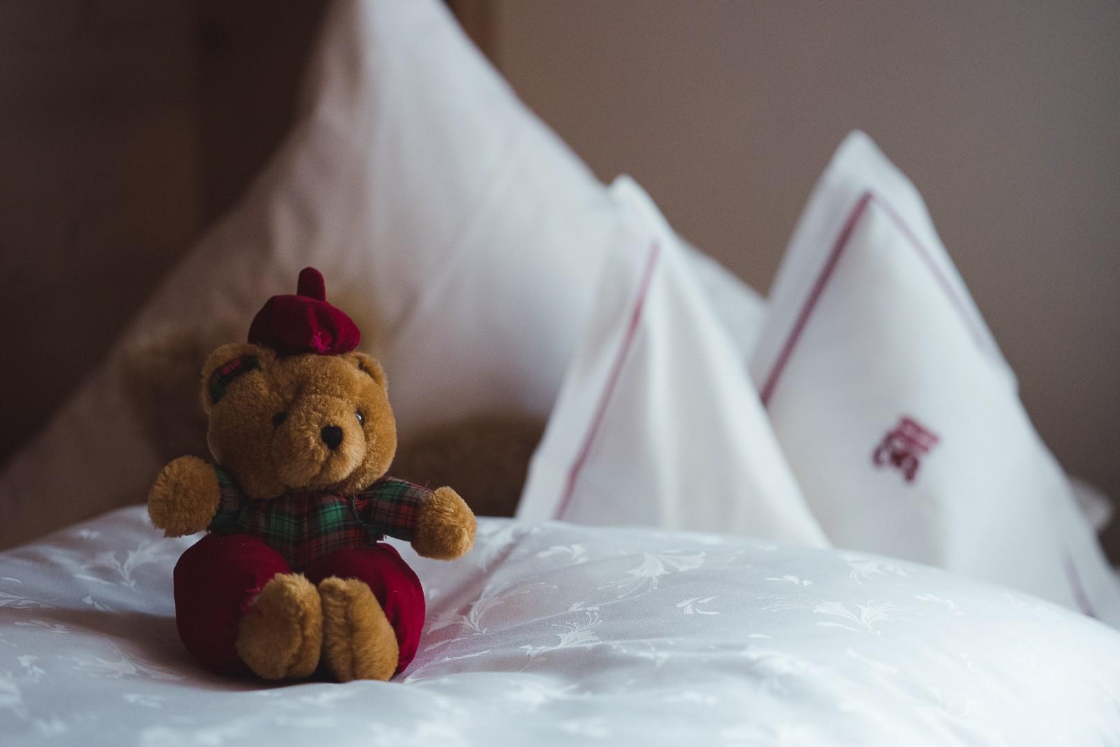 Teddybär auf Bett im Kinderzimmer im hotel und chalet madlochBlick in Lech am Arlberg.