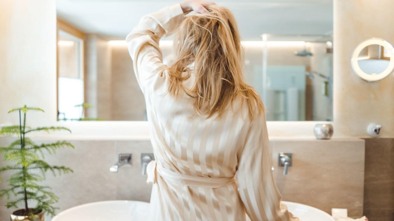 Eine blonde Dame, die sich im Spiegel begutachtet.