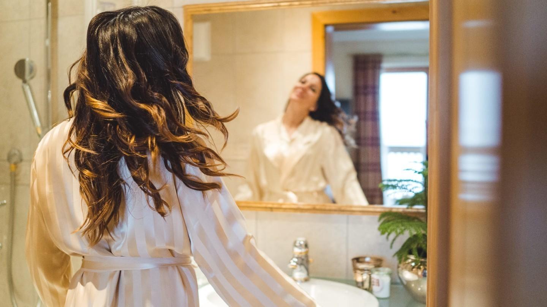 Eine Dame im Bad, die sich im Spiegel anschaut.