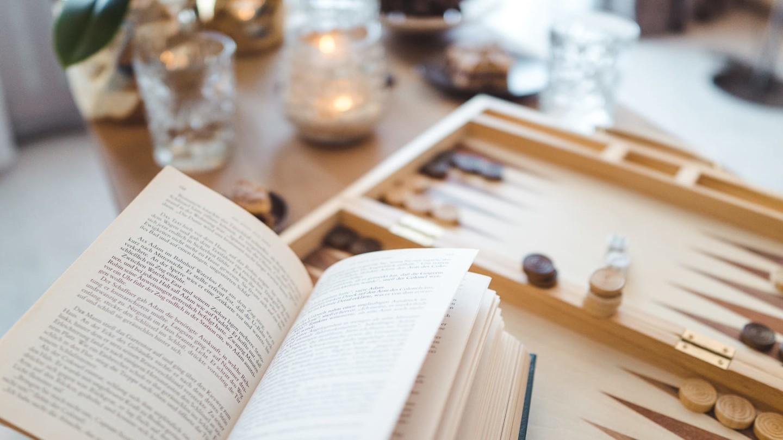 Brettspiel und Buch auf Wohnzimmertisch.