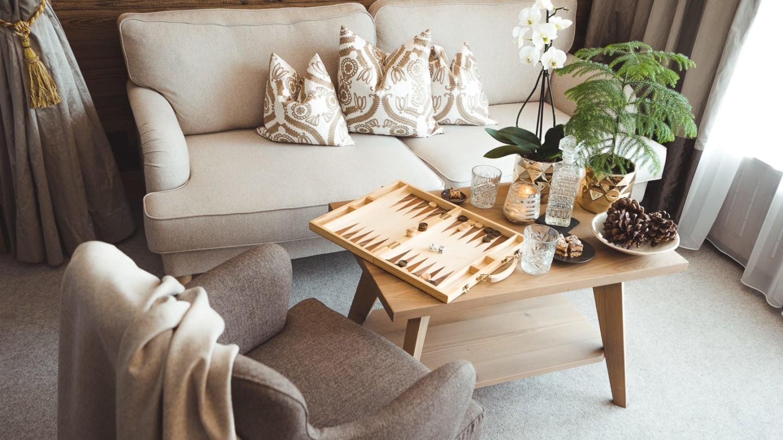 Wohnecke mit beiger Couch, braunem Fauteuil und Sofatisch.