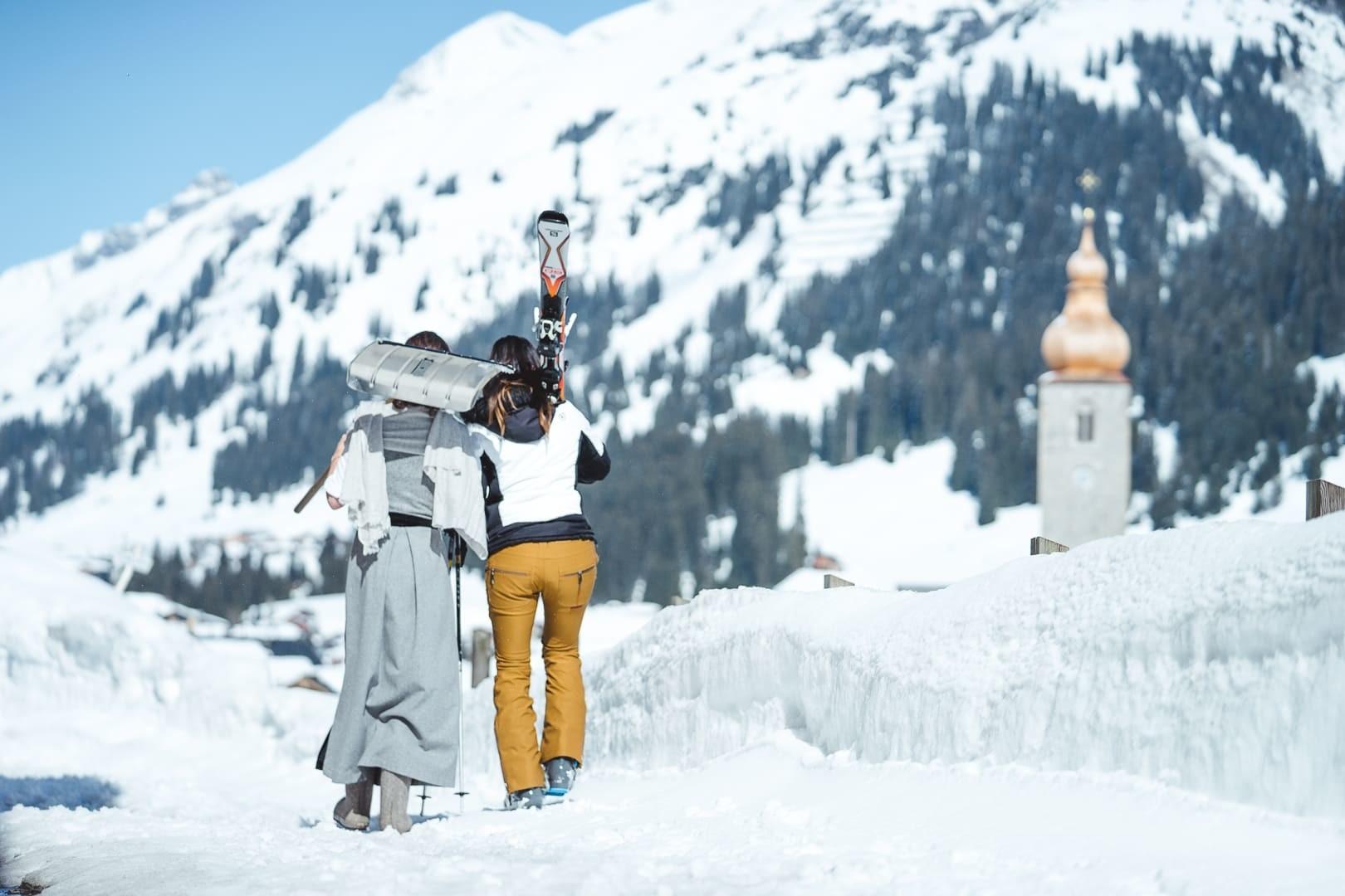 Zwei Damen, eine mit Ski, eine mit Dirndlkleid spazieren im Schnee nach Lech.