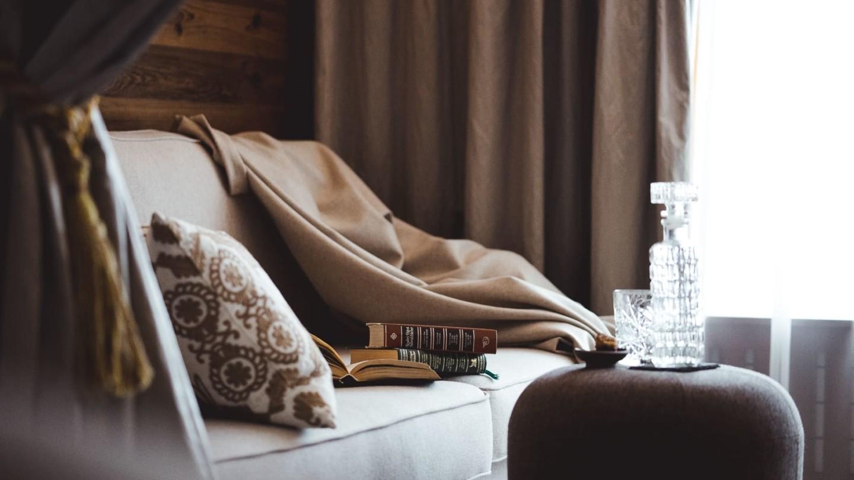 Wohnecke mit Couch und Hocker im Familienzimmer Bergblick.