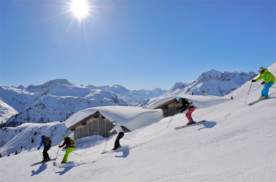 Eine Skigruppe bei der Abfahrt am Arlberg mit einem Skilehrer der Skischule Lech.