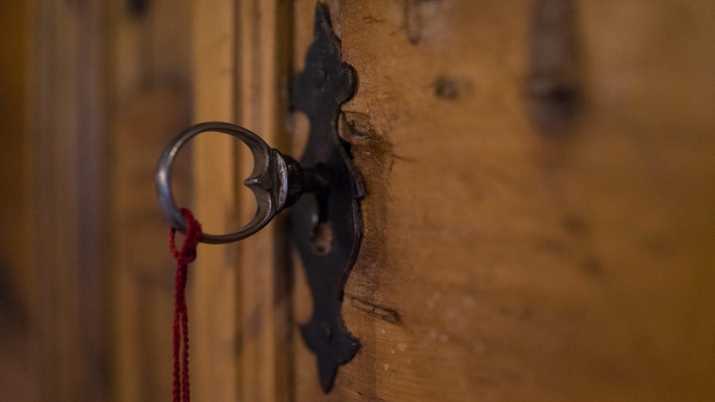 Alter Eisenschlüssel im Schloss einer Holztür.