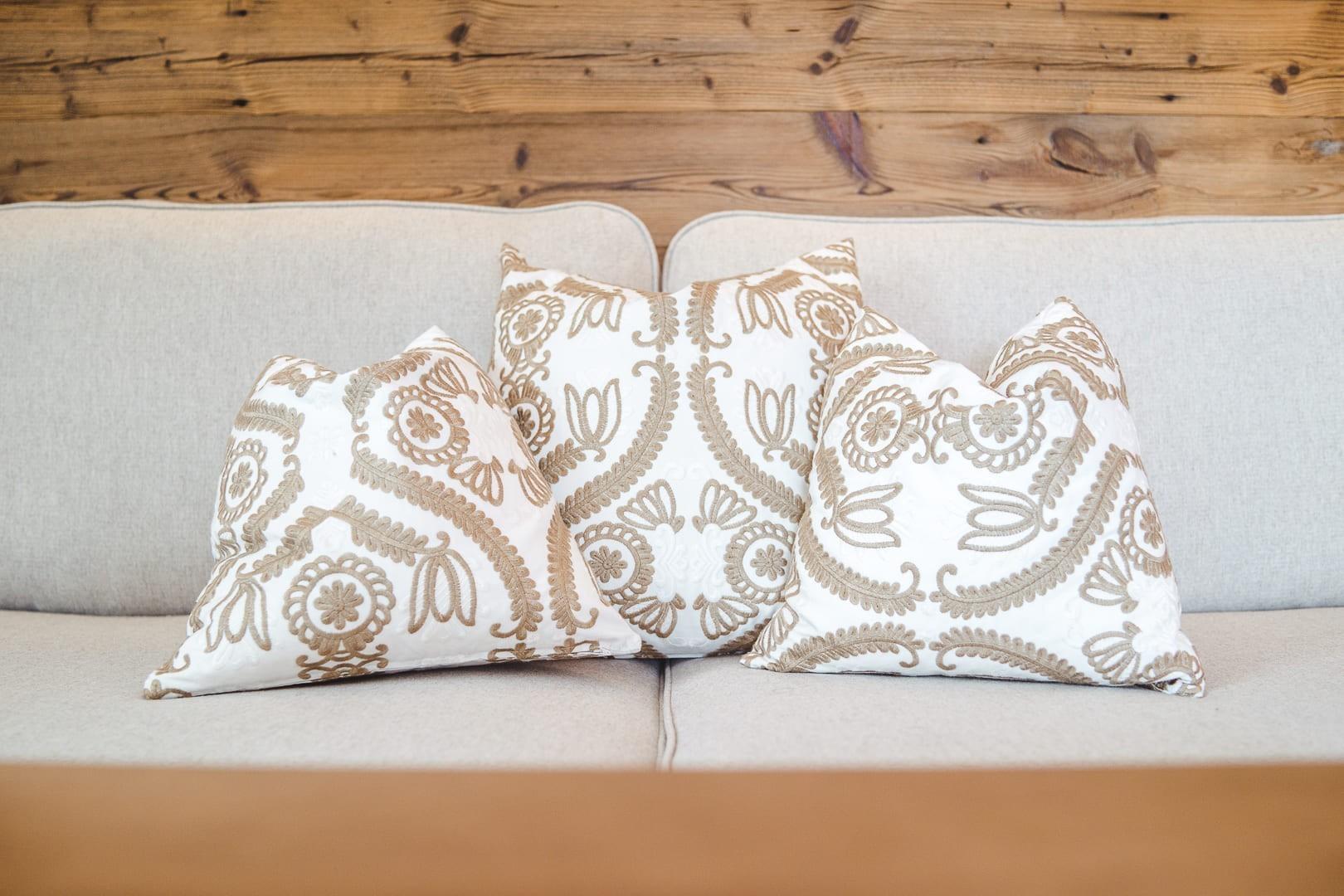 Drei schöne Pölster auf einer beigen Couch.