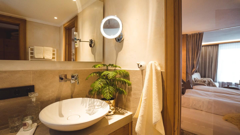 Badezimmer mit Fenster und Blick ins Schlafzimmer im hotel & chalet madlochBlick in Lech.