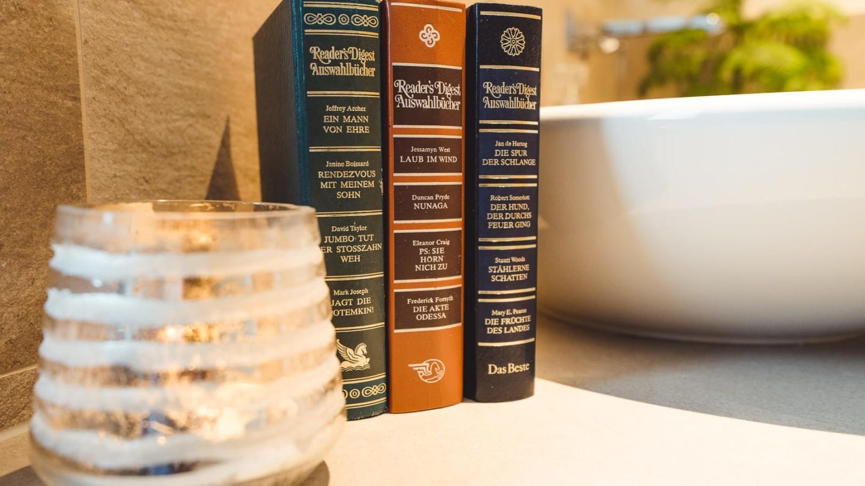 Drei Bücher und Kerzenlicht im Badezimmer des madlochBlick.
