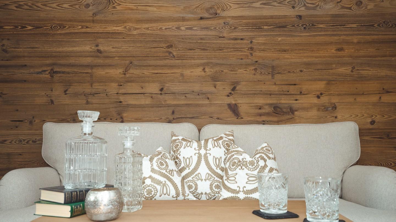 Beiges Sofa mit Tisch und Gläsern darauf im hotel madlochBlick.