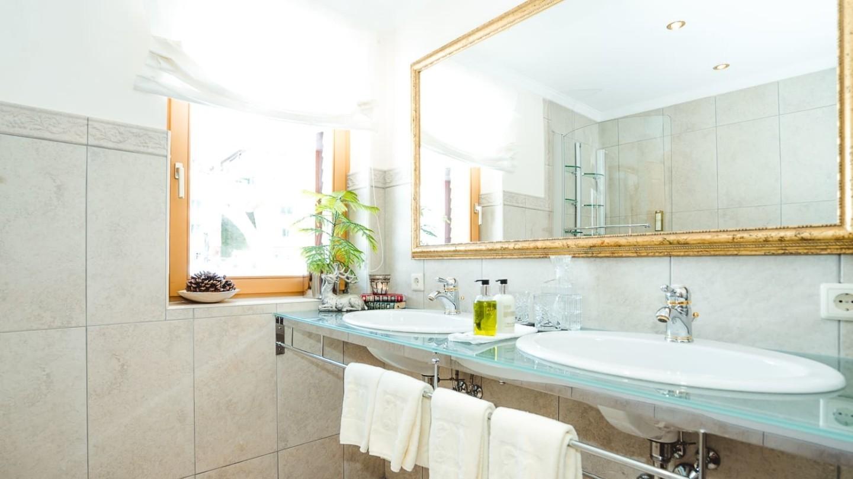 Badezimmer mit Doppelwaschbecken in der Junior Suite Kriegerhorn.