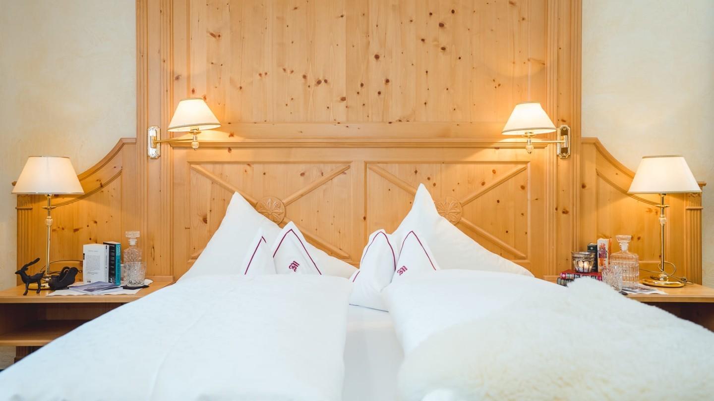 Doppelbett mit Holzvertäfelung und schöner Beleuchtung im Zimmer Kriegerhorn.