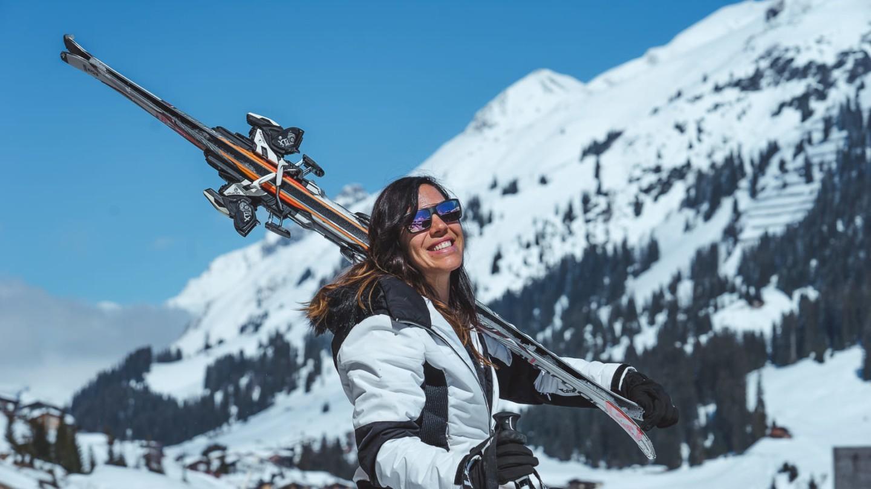 Eine Dame mit Ski auf den Schultern lacht in die Sonne und freut sich über Ski-in Ski-out im hotel madlochBlick.