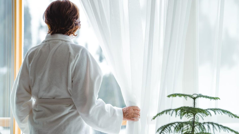 Eine Dame blickt vom Balkon des Zimmer Lechpanorama nach Lech.