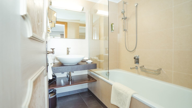 Badezimmer mit Badewanne und Waschbecken im Zimmer Omesberg im Hotel in Lech.