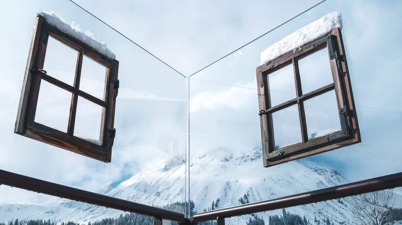 Ausblick durch eine Glasfront mit zwei Fenstern zum Omeshorn von der PanoramaTerrasse des hotel madlochBlick in Lech am Arlberg.