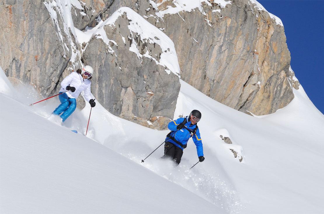 Skilehrer mit einer erwachsenen Dame im Privatskikurs bei der Skischule Lech.