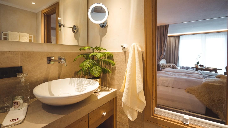 Badezimmer mit Blick ins Schlafzimmer im Zimmer Schafberg im hotel madlochblick.