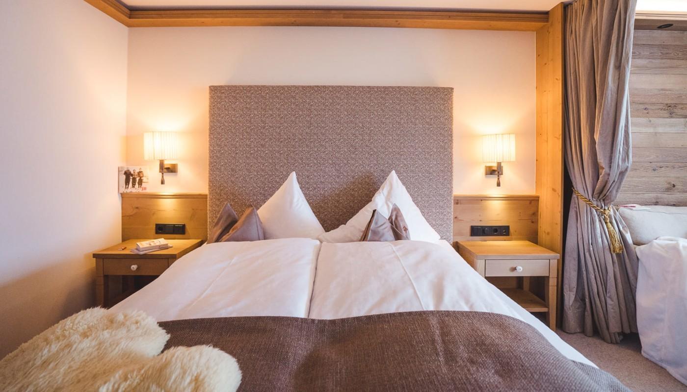 Doppelbett mit romantischer Beleuchtung im Schlafzimmer Schlegelkopf im hotel in Lech.