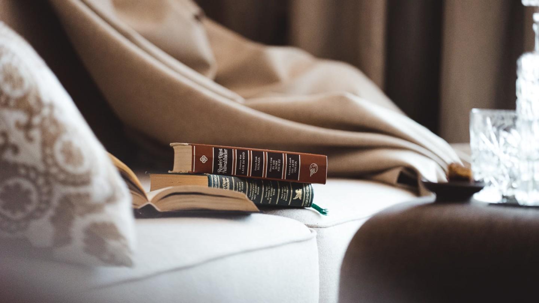 Wohnecke mit Büchern, Pölstern und Decke im Zimmer Schlegelkopf.