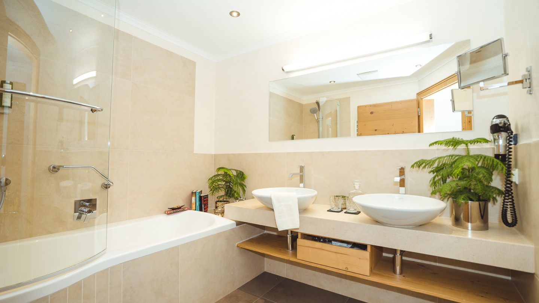 Badezimmer mit Badewanne und Doppelwaschbecken in der Suite Karhorn im hotel & chalet madlochBlick in Lech.