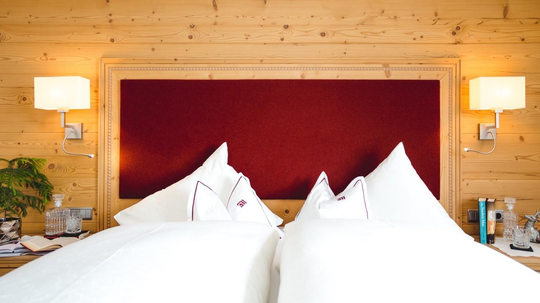 Doppelbett mit stimmungsvoller Beleuchtung in der Suite Karhorn im hotel & chalet madlochBlick in Lech.