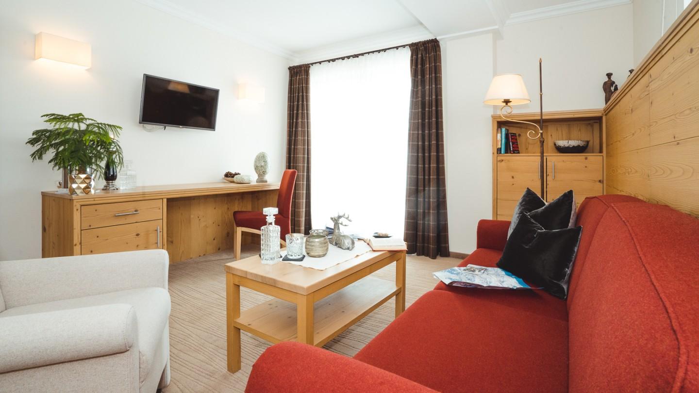 Wohnbereich mit Couch, Tisch und Stehlampe in der Suite Karhorn im hotel & chalet madochBlick in Lech am Arlberg.