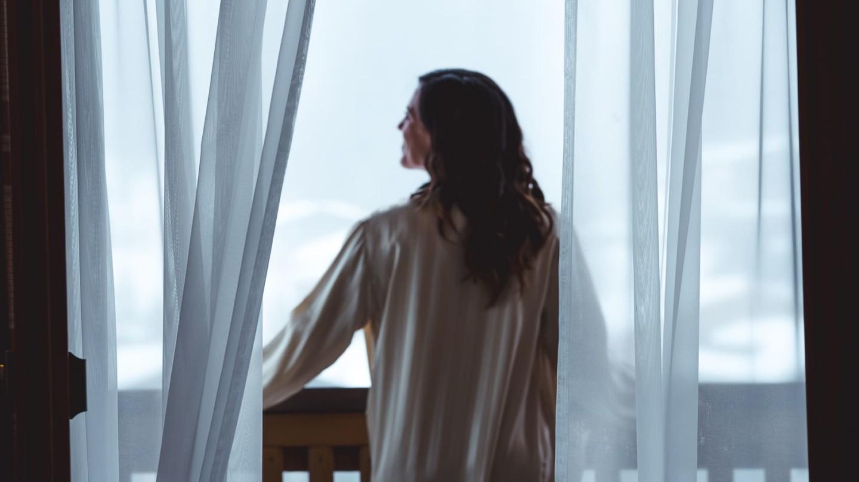 Eine Dame am Balkon der Suite Rüfikopf, die die Aussicht über Lech geniesst.