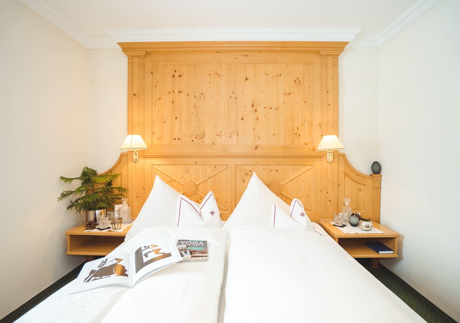 Doppelbett mit Holzvertäfelung in der Suite Rüfikopf im hotel & chalet in Lech.