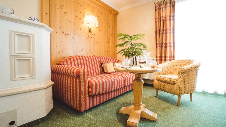 Wohnecke mit Kachelofen in der Suite Rüfikopf im hotel & chalet madlochBlick in Lech.