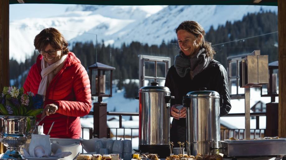 Zwei Inhaberdamen beim Winterpicknick auf der Terrasse des hotel und chalet madlochBlick in Lech am Arlberg.