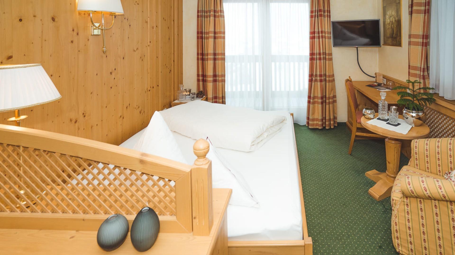 Grand Lit mit Schreibtisch, Sitzgelegenheit und Balkon im Schlafzimmer Wöster im Hotel in Lech.